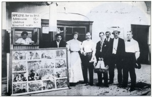 Marie de Kerstrat (o) (at the ticket counter) and her son Henry (fifth from the right) in front of their St. Louis moving picture show. GRAFICS.